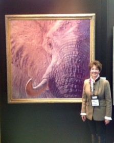 Rita Schimpff of Heritage Game Mounts next to 'Tusk' by John Banovich at convention